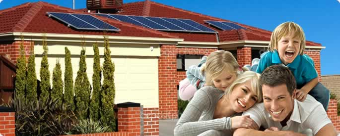 a family in front of their house with solar panels on the roof